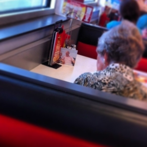 woman in restaurant looks at pic of husband