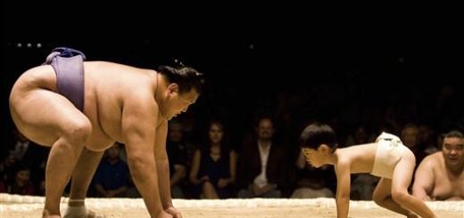 Sumo wrestler wrestling child