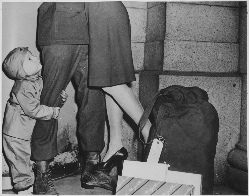 little boy clings to soldier father's leg
